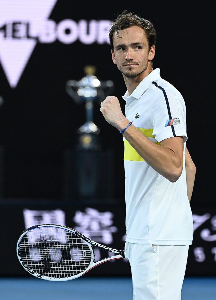 Daniil Medvedev comemora ponto contra Tsitsipas com a taça do Australian Open ao fundo