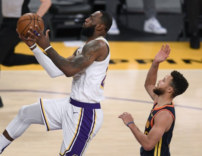 LeBron James, do Los Angeles Lakers, faz pontos sobre Stephen Curry, do Golden State Warriors, no Staples Center — Foto: Harry How/Getty Images
